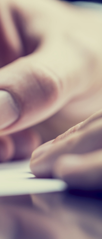 Close up of a hand holding a pen to paper