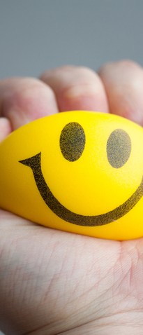 A hand squeezing a yellow stress ball with a smiley face on it